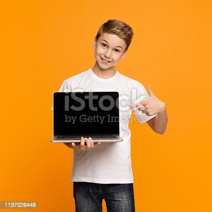 istock Happy smiling boy pointing at laptop computer 1137026449
