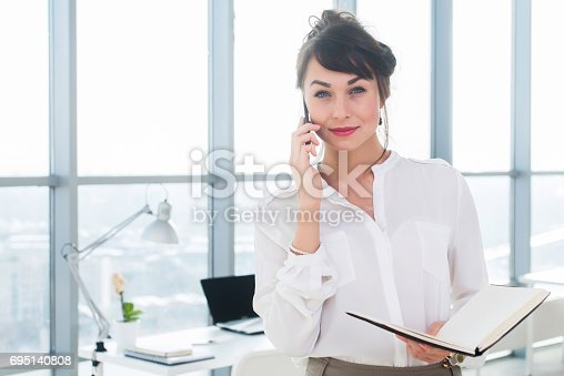 istock Happy smiling businesswoman having a business call, discussing meetings, planning her work day, using smartphone. 695140808
