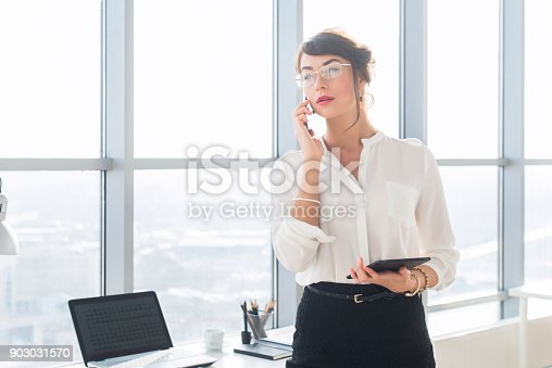 istock Happy smiling businesswoman having a business call, discussing meetings, planning her work day, using smartphone. 903031570