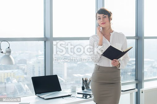 istock Happy smiling businesswoman having a business call, discussing meetings, planning her work day, using smartphone. 953202578