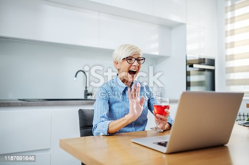 Happy smiling caucasian blonde senior woman sitting at dining table, drinking red wine, having video call over at laptop and waving.