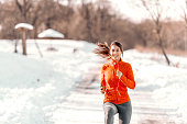 Happy smiling Caucasian woman in sportswear standing on the trail with earphones on and listening to music. Winter fitness concept.
