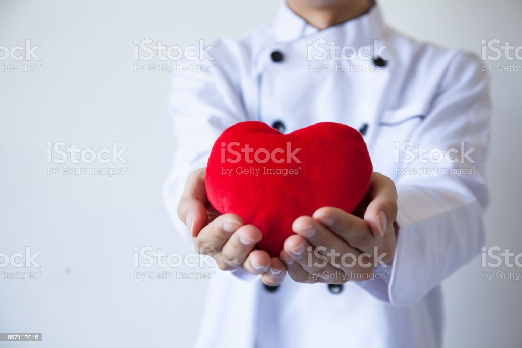 Happy smiling chef holding heart shape with love and passion stock photo