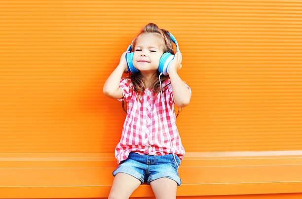 glücklich lächelnd kind genießt hört musik im kopfhörer - sommer teenagermode stock-fotos und bilder
