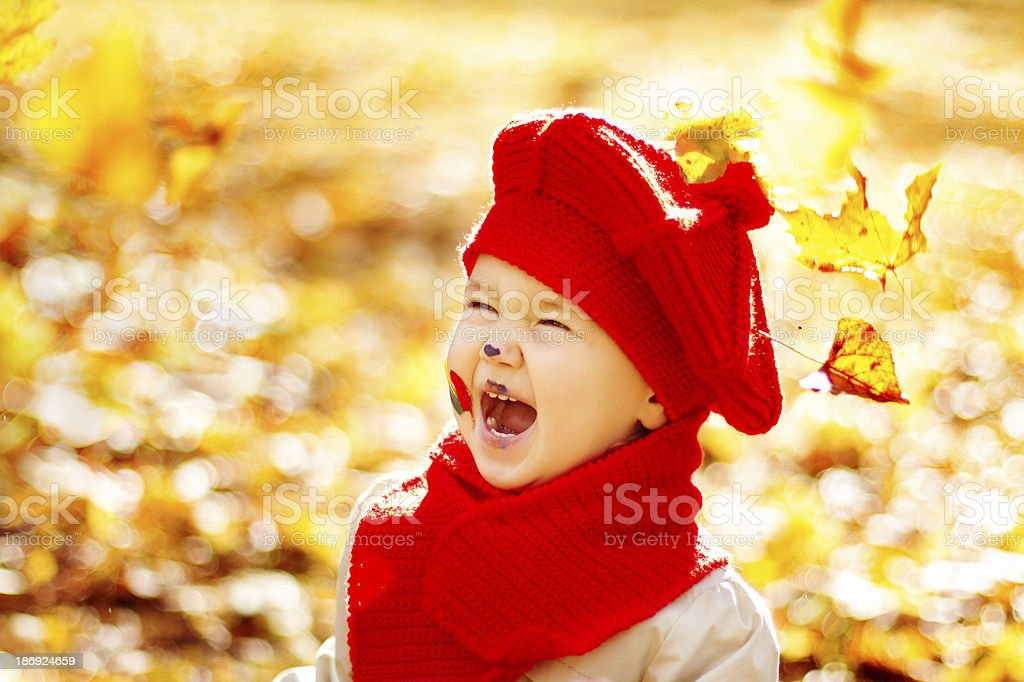 Happy smiling child in yellow autumn park, red hat royalty-free stock photo