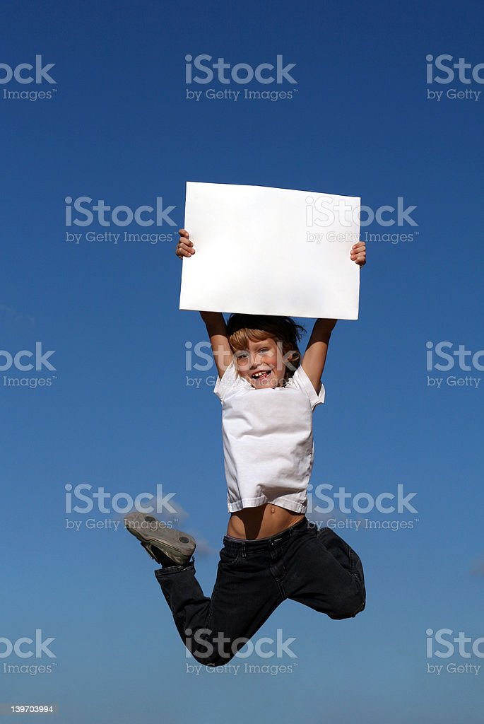 happy smiling child jumping with blank board sign or poster royalty-free stock photo