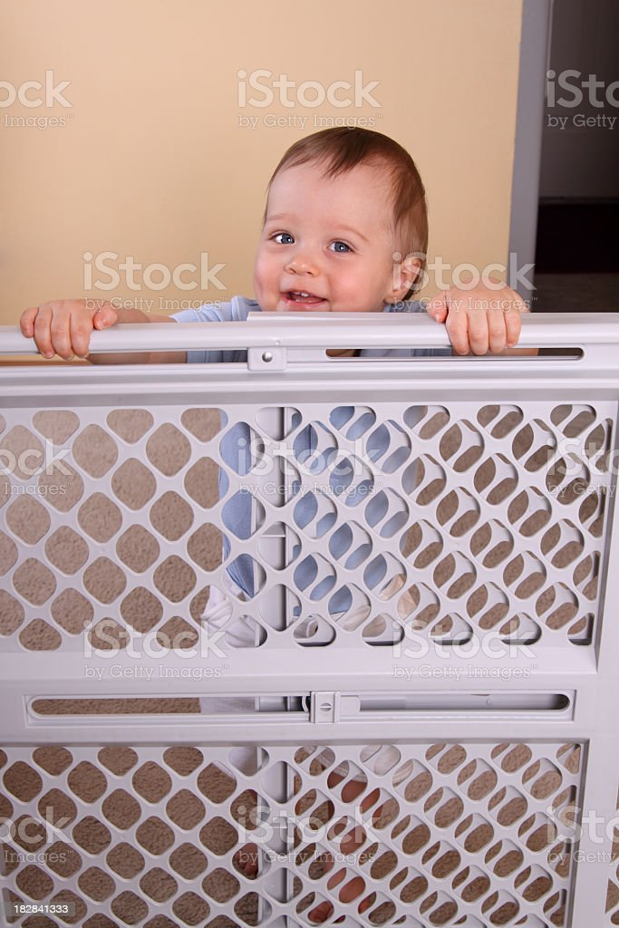 A happy smiling child over a child proofing fence stock photo