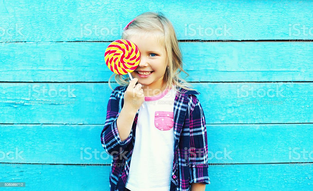 Happy smiling child with sweet lollipop having fun over blue stock photo