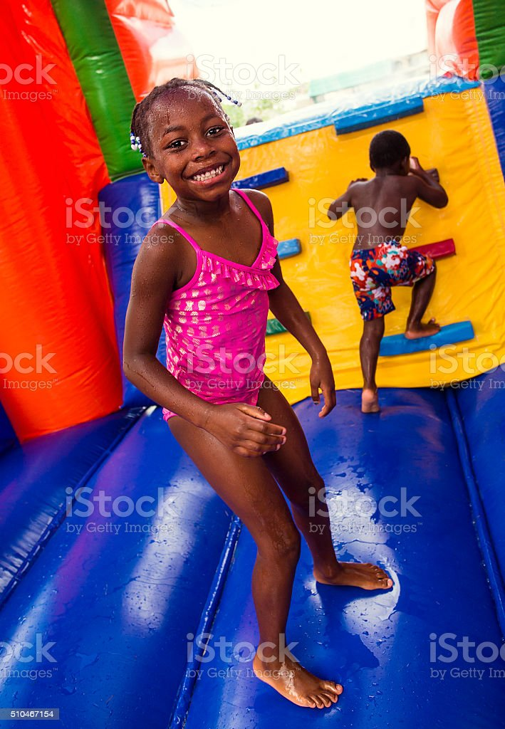 Happy smiling children playing on an inflatable bounce house stock photo