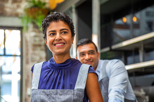 Happy, smiling couple of owners/co-workers in small cafe with woman in foreground and man in background (soft focus): small business, Pacific Islander, Indian and Latin American & Hispanic ethnicities