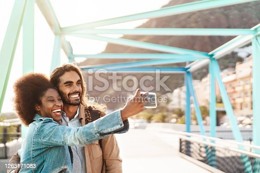 Happy smiling couple taking selfie with mobile smartphone outdoor - Young trendy people having fun during vacations - Social people technology addicted and travel trend lifestyle concept
