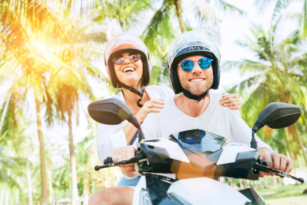 Happy smiling couple travelers riding motorbike scooter in safety helmets during tropical vacation under palm trees Happy smiling couple travelers riding motorbike scooter in safety helmets during tropical vacation under palm trees indochina stock pictures, royalty-free photos & images