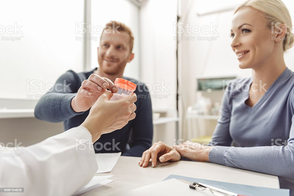 Happy smiling couple visiting doctor stock photo