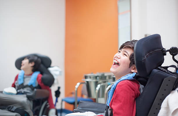 Happy, smiling disabled boy in wheelchair waiting in doctor's office stock photo