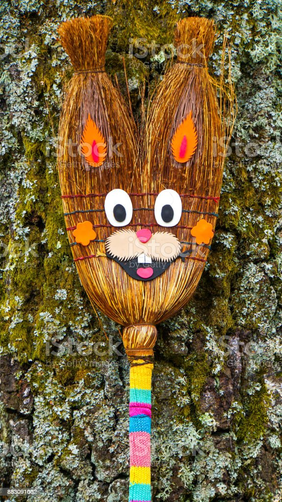 Happy smiling easter bunny before a brown trunk made of a broom stock photo