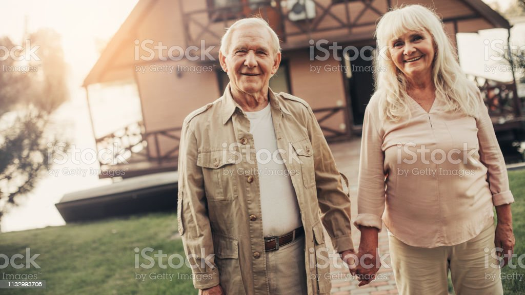 Cheerful mature twosome standing fronting house and looking at camera...