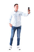 Happy smiling elegant adult man taking selfie with smart phone. Full body isolated on white background.