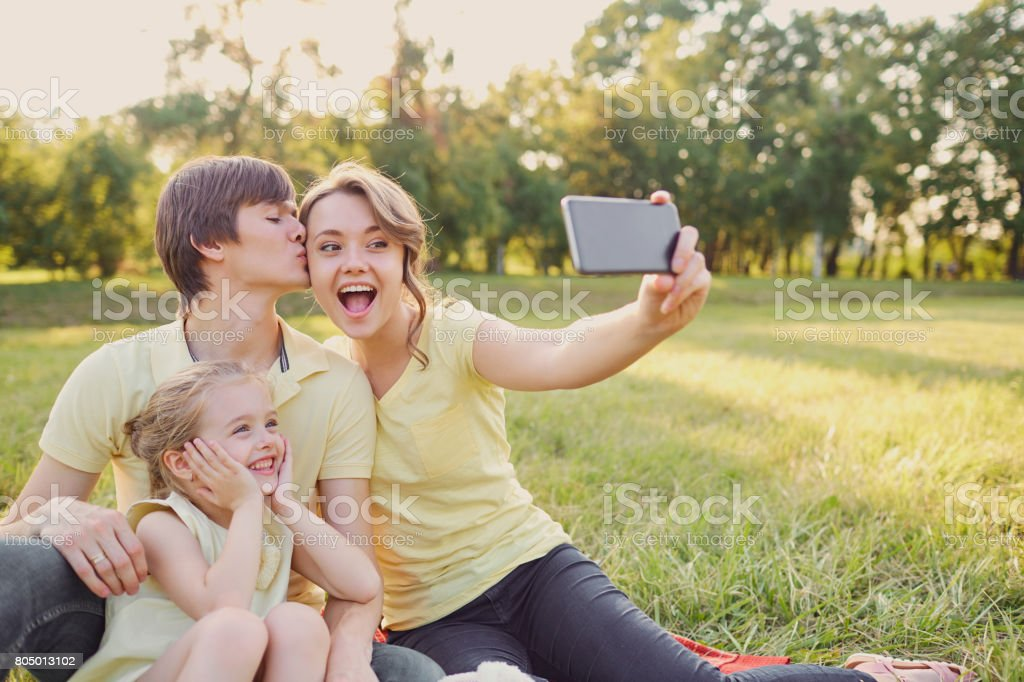 Happy smiling family being photographed in the park stock photo
