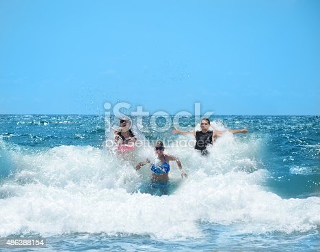 istock Happy smiling family having fun in the beautiful ocean. 486388154