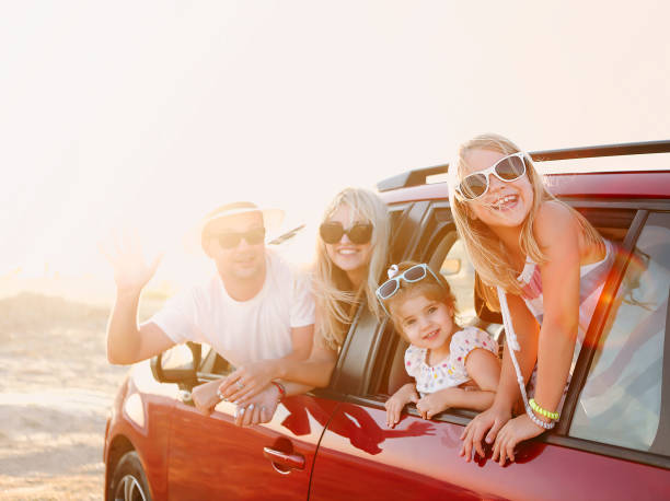 Happy smiling family with daughters in the car with sea background stock photo
