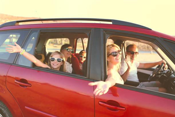 felice famiglia sorridente con figlie in macchina con sfondo mare - auto foto e immagini stock