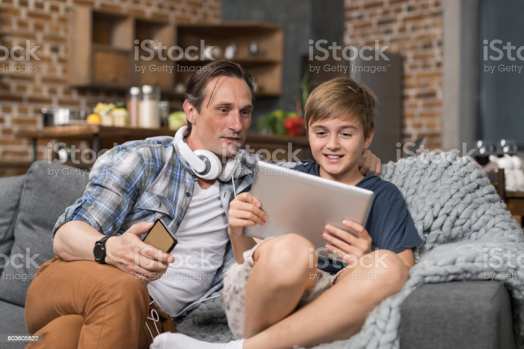 Happy Smiling Father And Son Sitting On Couch Use Tablet Computer, Parent Spending Time Child stock photo