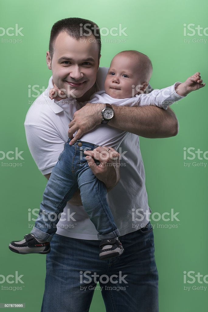 Happy smiling father embracing his baby boy stock photo