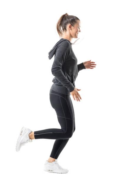 glücklich lächelnd weibliche jogger laufen in zip sweatshirt mit kapuze und leggings - zip hoodies stock-fotos und bilder
