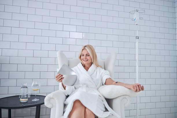 Happy smiling female receiving intravenous vitamin therapy in beauty clinic stock photo