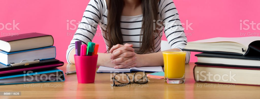 Happy smiling female student sitting at her desk filled with textbooks stock photo