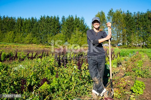 Happy vegetable farmer on a small scale organic farm in the field.  Full length portrait with a nice big smile.  Real person, real life.