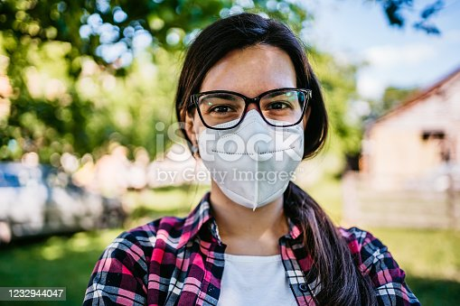 Close up portrait of happy young Caucasian smiling female wearing N-95 protective face mask outdoors.