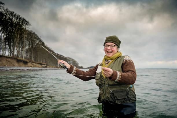 glücklich lächelnd fliegenfischer trieb ihre linie - angeln dänemark stock-fotos und bilder