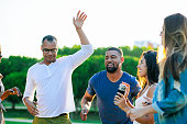 Happy smiling friends dancing in park. Young people listening music and relaxing together. Leisure concept