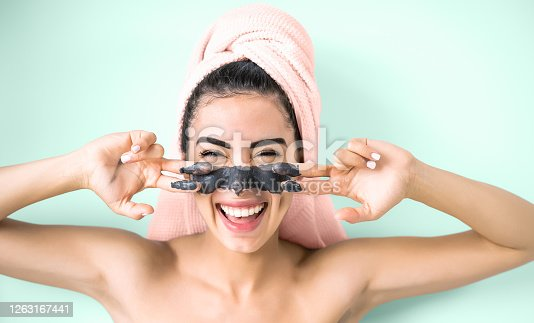 istock Happy smiling girl applying facial charcoal mask portrait - Young woman having skin care cleanser spa day - Healthy beauty clean treatment and cosmetology products concept - Aquamarine background 1263167441