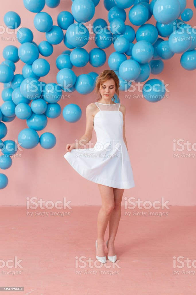 Happy smiling girl in cute white dress dancing on pink background. Modern studio decorated with blue shiny balls royalty-free stock photo