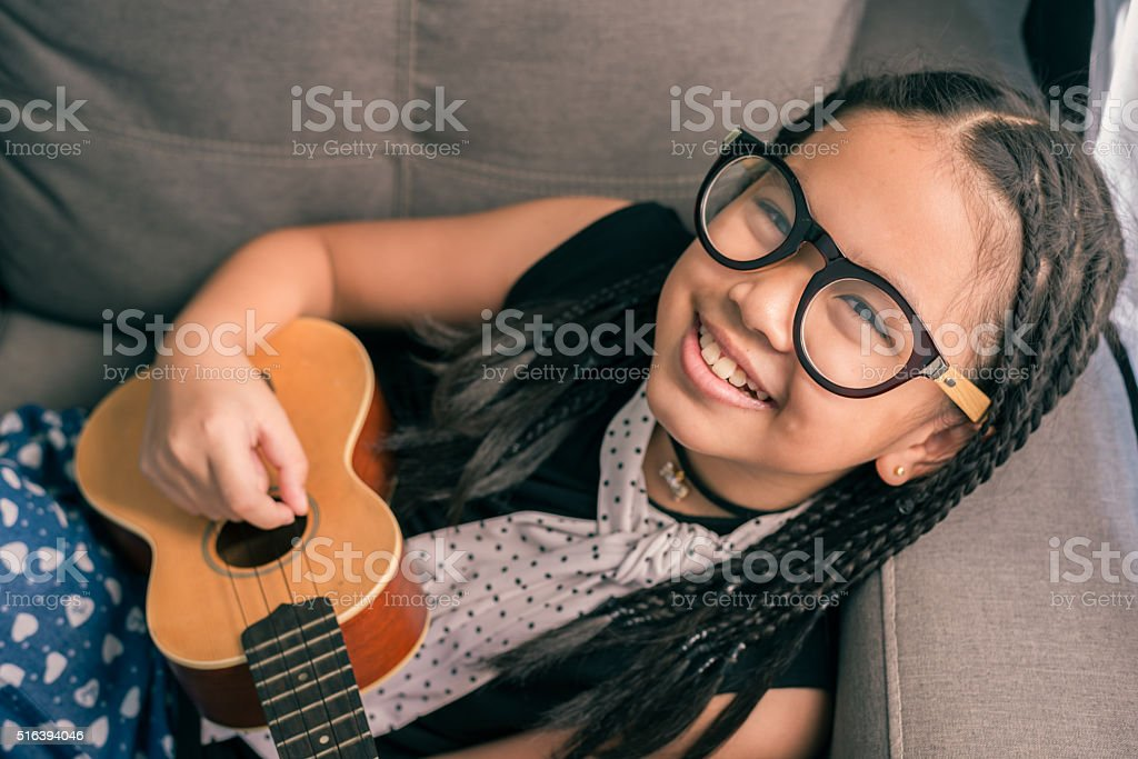 Happy smiling girl ,learning to play the acoustic guitar stock photo
