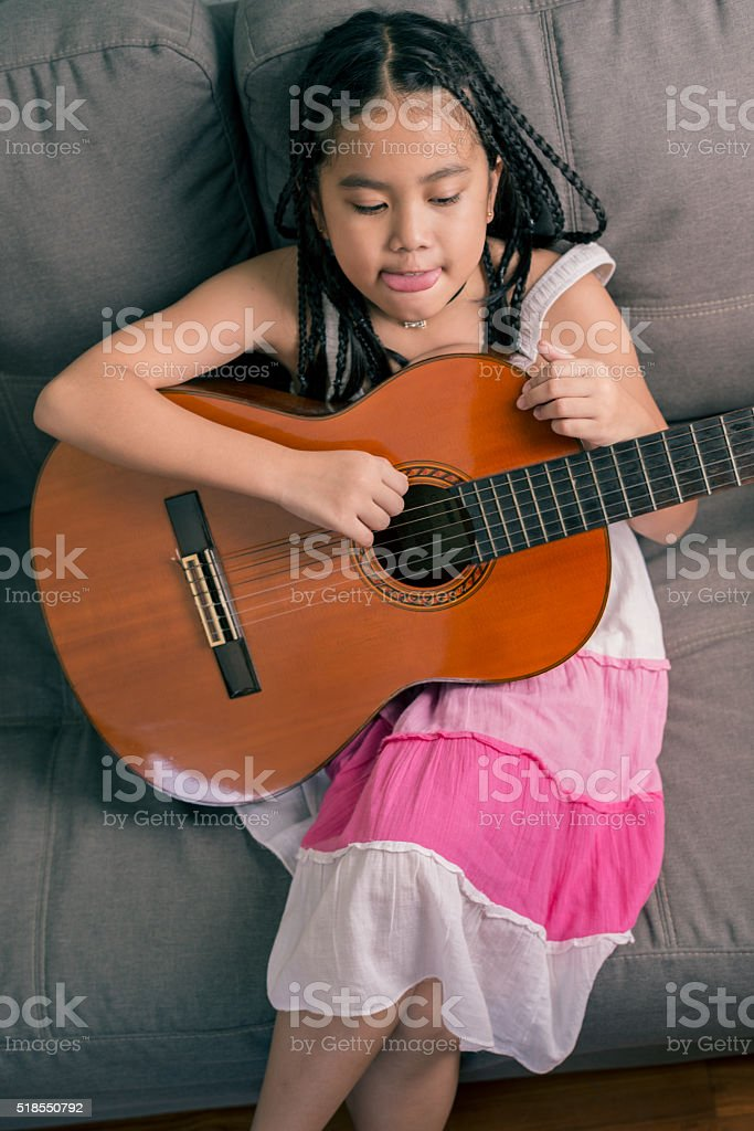 Happy smiling girl learning to play the acoustic guitar stock photo