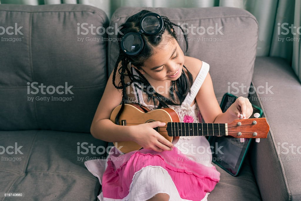 Happy smiling girl learning to play the music stock photo