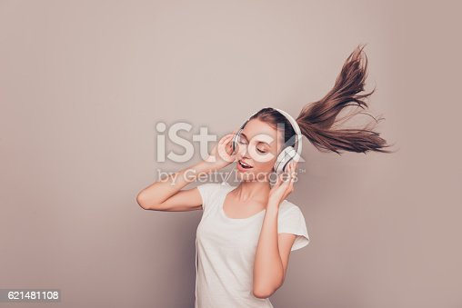 istock happy smiling girl listening music in headphones and singing 621481108