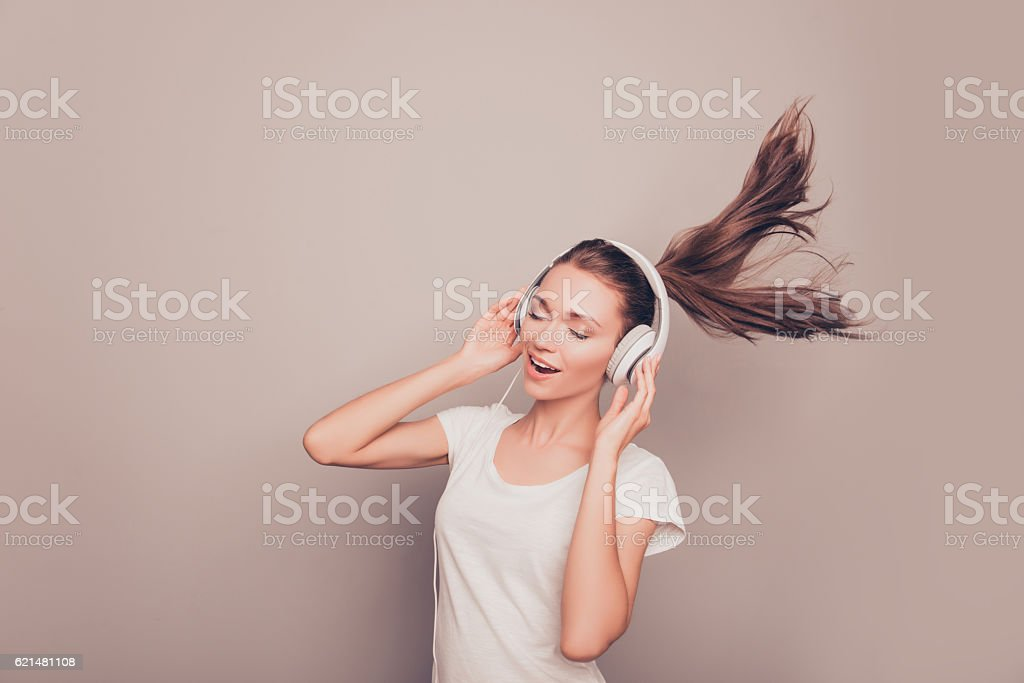 happy smiling girl listening music in headphones and singing stock photo