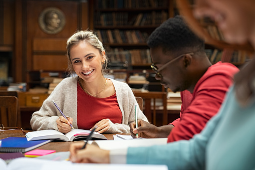 istock Happy smiling girl studying in university library 1201407370