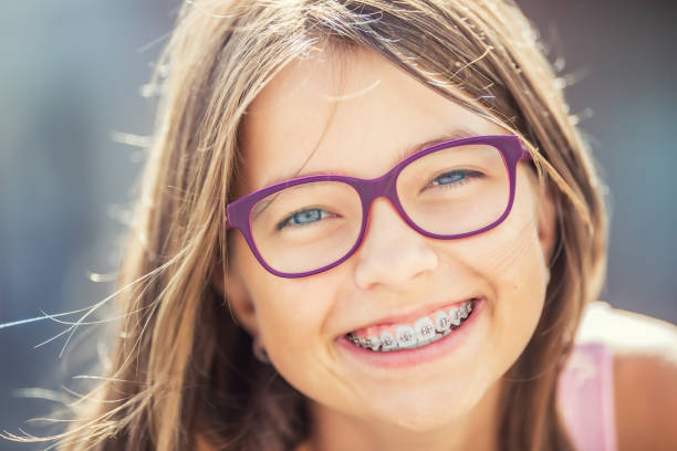 Happy smiling girl with dental braces and glasses. Young cute caucasian blond girl wearing teeth braces and glasses stock photo
