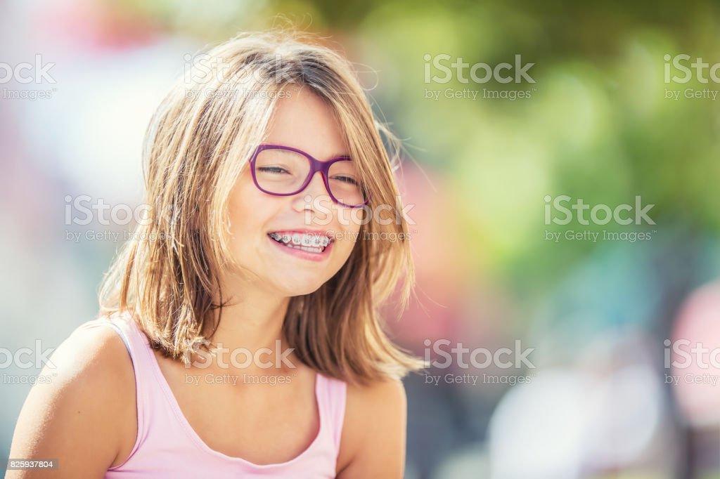 Glücklich lächelnde Mädchen mit Zahnspangen und Gläser. Junge süße kaukasische blonde Mädchen tragen Zähne Zahnspange und Brille - Lizenzfrei Atelier Stock-Foto