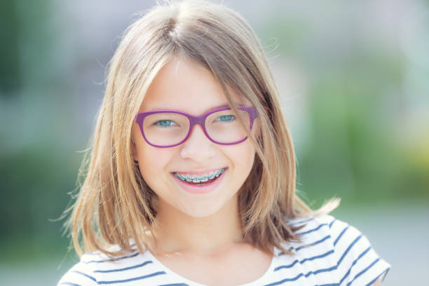 Cтоковое фото Happy smiling girl with dental braces and glasses. Young cute caucasian blond girl wearing teeth braces and glasses