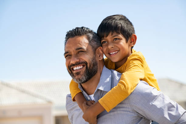 Happy smiling indian father giving son ride on back stock photo