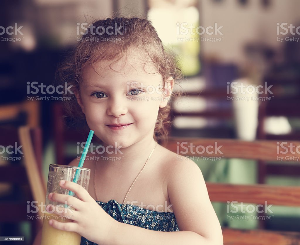 Happy smiling kid girl drinking fresh juice from glass in cafe. Toned...