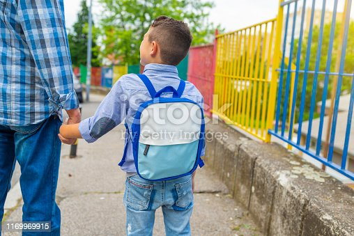 Happy smiling kid is going to school for the first time. Child boy with bag go to elementary school. Child of primary school. Pupil go study with backpack. Back to school
