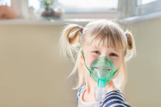 Happy smiling kid using nebuliser mask. Inhalation therapy curing chest cold and coughing. Healthcare and disease prevention concept Happy smiling kid using nebuliser mask. Inhalation therapy curing chest cold and coughing. Healthcare and disease prevention concept. smoke inhalation stock pictures, royalty-free photos & images