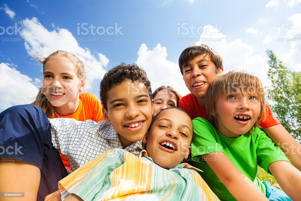 Happy smiling kids sitting in a hug close outside stock photo